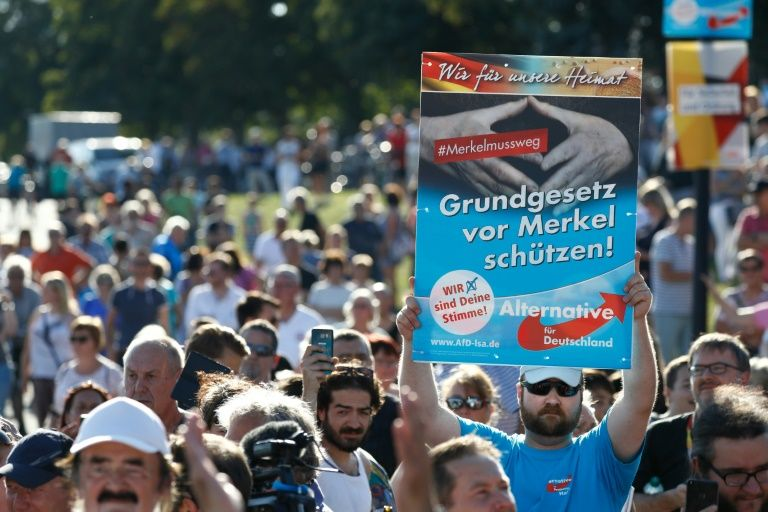 """At one of Merkel's recent campaign rallies, a supporter of the populist Alternative for Germany (AfD) party held a placard saying """"Protect the constitution from Merkel"""""""