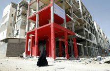 A Palestinian veiled woman walks past a building which was destroyed during the 50-day war between Israel and Hamas-led militants in the summer of 2014, in the northern Gaza Strip city of Beit Hanun, on May 9, 2016