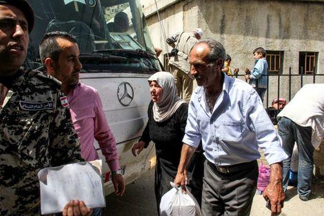 Des réfugiés syriens dans la localité libanaise de Chebaa se préparent le 18 avril 2018 à monter à bord de bus qui doivent les conduire dans leur village en Syrie