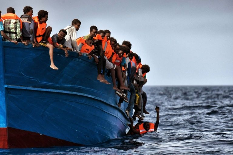 Migrants hang from a boat as they wait to be rescued as they drift in the Mediterranean Sea some 20 nautical miles north off the coast of Libya
