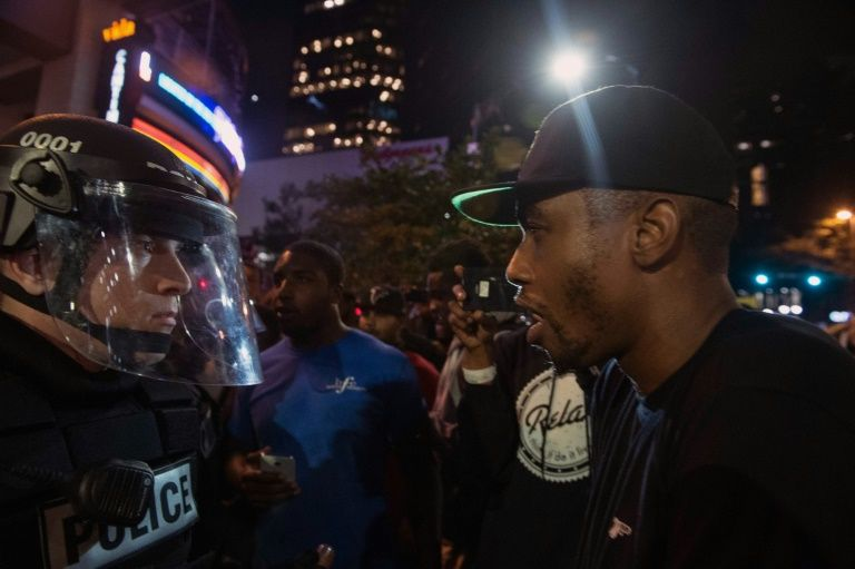 Several hundred people taunted riot police  in Charlotte, North Carolina during a second night of unrest ignited by the fatal police shooting of a black man
