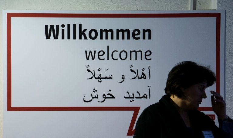 "A volunteer stands in front of a sign reading ""Welcome"" in German, English, Farsi and Arabic during the inauguration of a new jobs counseling center for migrants and refugees at the former Tempelhof Airport in Berlin, on January 27, 2016"