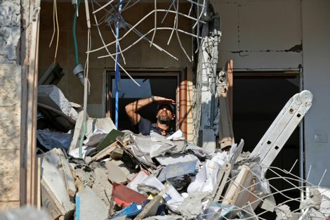 An Israeli sapper checks the rear of a family home in the southern city of Beersheba on October 17, 2018 after its garden was hit by a the first rocket fire from the Gaza Strip in weeks