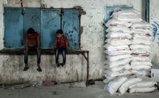 Palestinian children sit by sacks of food provided by the United Nations Relief and Works Agency in the Gaza Strip where 40 percent of the two million population are dependent on aid
