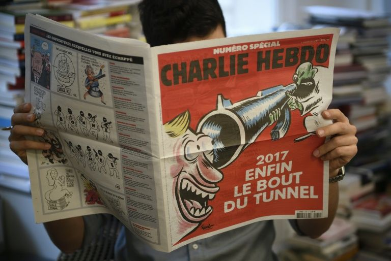 A man reads a special issue of French satirical magazine Charlie Hebdo on January 3, 2017