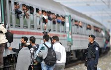A Croatian police officer looks on as migrants and asylum seekers board a train in the eastern Croatian village of Tovarnik, near the border crossing with Serbia, on September 24, 2015