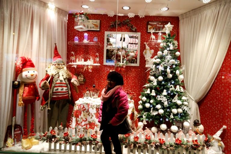 An Iranian girl poses for a picture infront of Christmas decorations outside a shop in the capital Tehran on Christmas Eve, December 24, 2016
