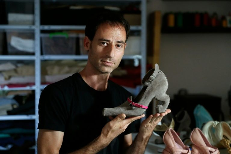 """Israeli shoe designer Kobi Levi poses in his workshop with one of his creations called """"Miao"""" in Tel Aviv"""