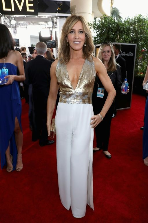 """""""American Crime"""" nominee Felicity Huffman sported a sleeveless Georges Chakra jumpsuit with a gold and silver bodice and white trousers at the 74th Annual Golden Globe Awards"""