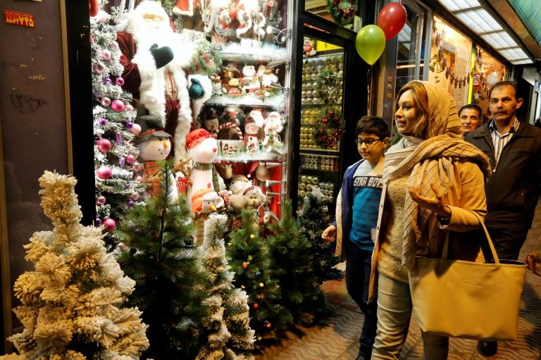 Iranians walk past Christmas decoration at a shop in the capital Tehran on Christmas Eve, December 24, 2016