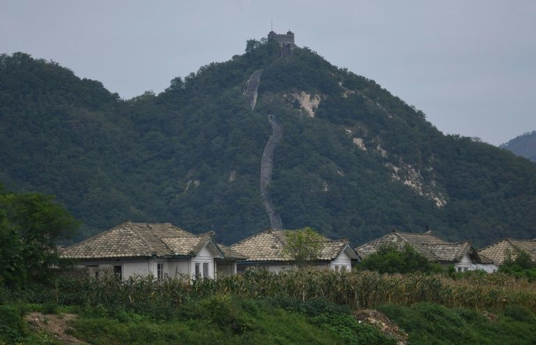 North Korean houses on an island in the Yalu river in front of the Hushan section of the Great Wall of China on September 12, 2016
