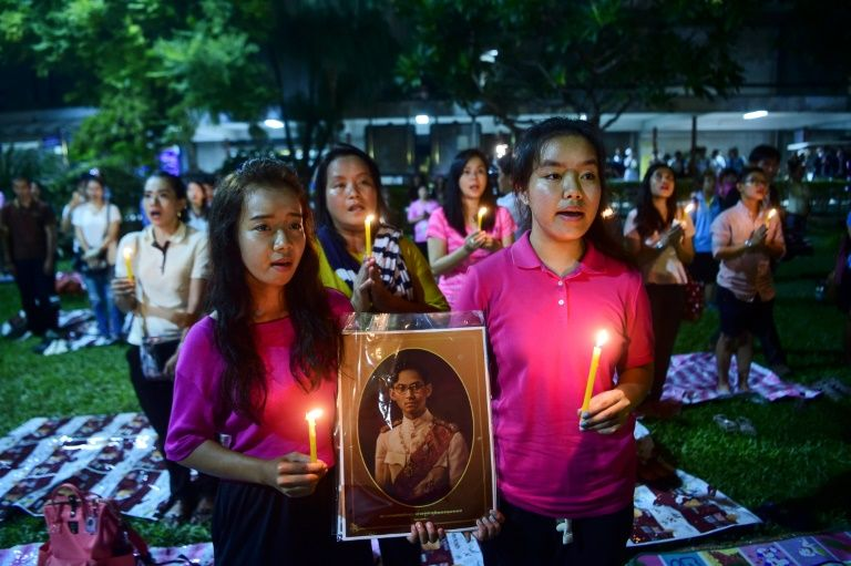 People hold a photo of Thailand's King Bhumibol Adulyadej as they react to his death on October 13, 2016 at Siriraj Hospital in Bangkok