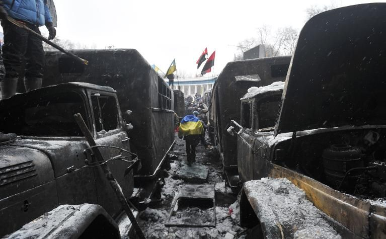 A protester wrapped in the Ukrainian flag walks between wreckages of burnt trucks after violent clashes in central Kiev on January 21, 2014