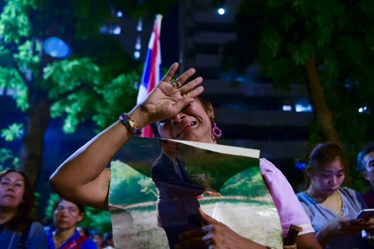 People react to news of the death of Thailand's King Bhumibol Adulyadej at Bangkok's Siriraj Hospital