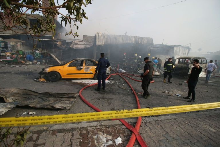 Security forces and emergency personnel gather at the site of a suicide bombing in the Baghdad Jadida area of the Iraqi capital on April 25, 2016