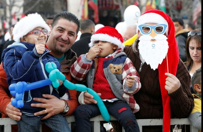 Palestinians attend a Christian scouts performance at Manger Square outside the Church of the Nativity in Bethlehem on December 24, 2016 during Christmas celebrations in the city in the Israeli-occupied West Bank