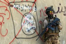 An Iraqi soldier stands next to a wall with a red cross drawn through a slogan of the Islamic State (IS) group, in Fallujah