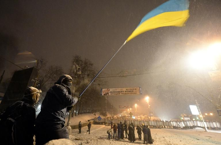An opposition activist waves an Ukrainian flag as he stands on a barricade in central Kiev early January 22, 2014