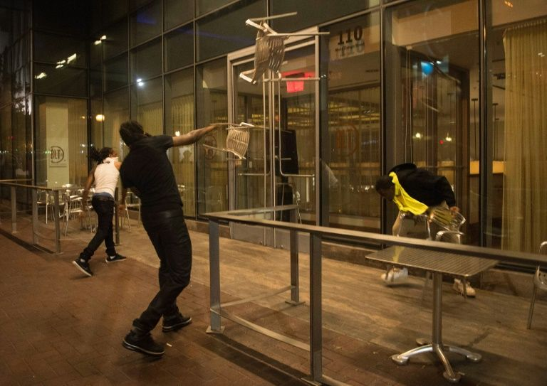 Protesters throw chairs at a restaurant in Charlotte, North Carolina, where racial tensions soared a day after a black man was killed by officers