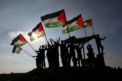 Palestinian protesters wave their national flag near the Israel-Gaza border east of the southern Gaza Strip city of Khan Yunis on January 9, 2018 as they demonstrate against calls for the closure of UNRWA by the Israeli prime minister and cuts in Palestin