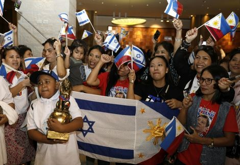 Filipinos wave their flag and the Israeli one as they wait for Philippine President Rodrigo Duterte to arrive in Israel for an official visit, on September 2, 2018