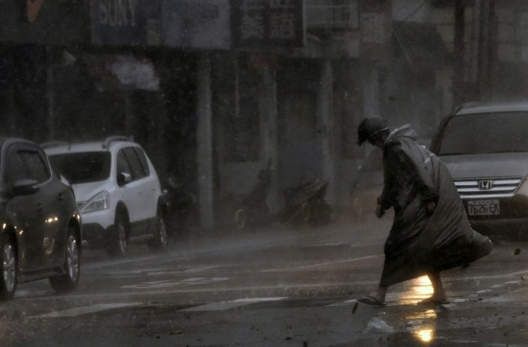 A man battles throught the wind and rain in New Taipei City as Typhoon Megi hits eastern Taiwan on September 27, 2016