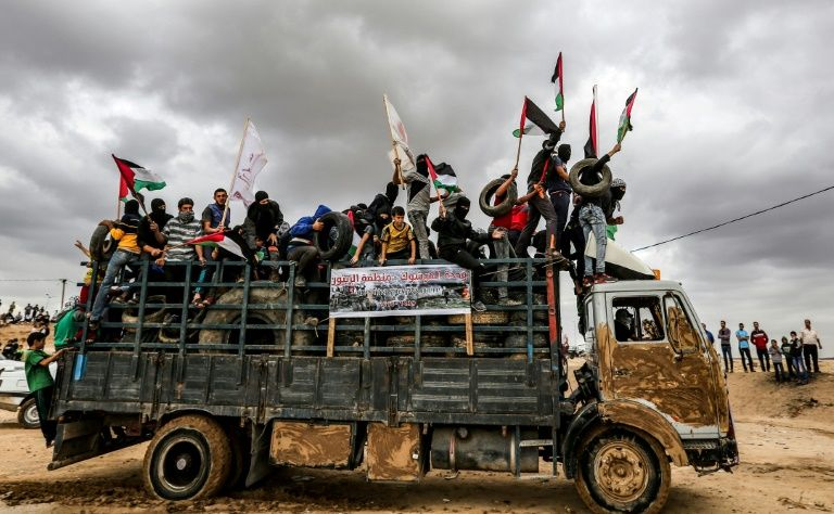 Gaza protesters ride in a truck waving Palestinian flags as they bring tyres to burn for cover during clashes along the border with Israel east of Gaza City on October 26, 2018