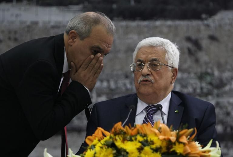 Director of Palestinian General Intelligence in the West Bank Majid Faraj (L) whispers to Palestinian President Mahmud Abbas during a meeting where he requested to join 15 United Nations agencies, in the West Bank city of Ramallah on April 1, 2014