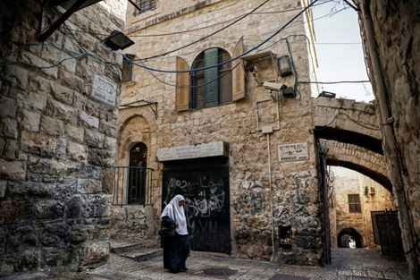 A Palestinian woman walks past a house in the Muslim Quarter of Jerusalem's Old City that was bought by Israeli settlers