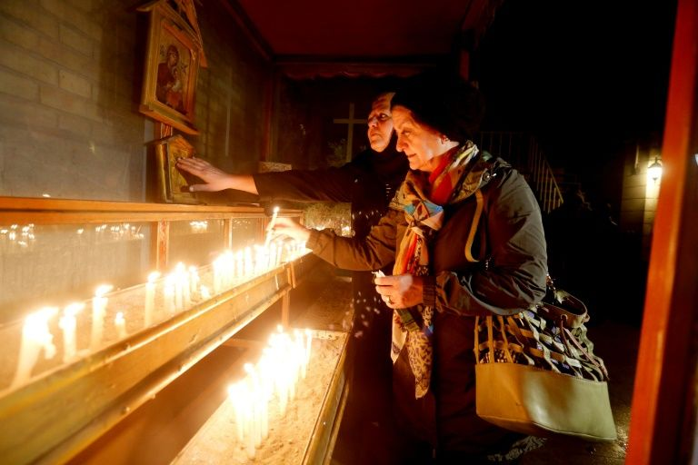 An Iranian woman lights a candle during Christmas Eve mass at the St Joseph Armenian Catholic church in Tehran