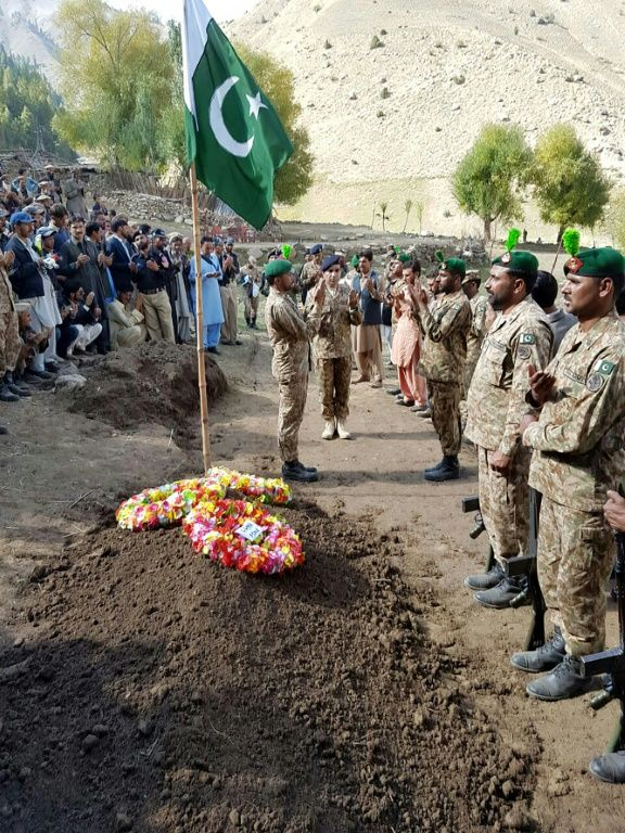 Pakistani troops lay a wreath at the grave of a soldier killed in firing along the Line of Control that divides the disputed territory of Kashmir, during his funeral in the Astore district of the Gilgit-Baltistan region