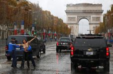Police stop topless female protester approaching Trump motorcade in Paris