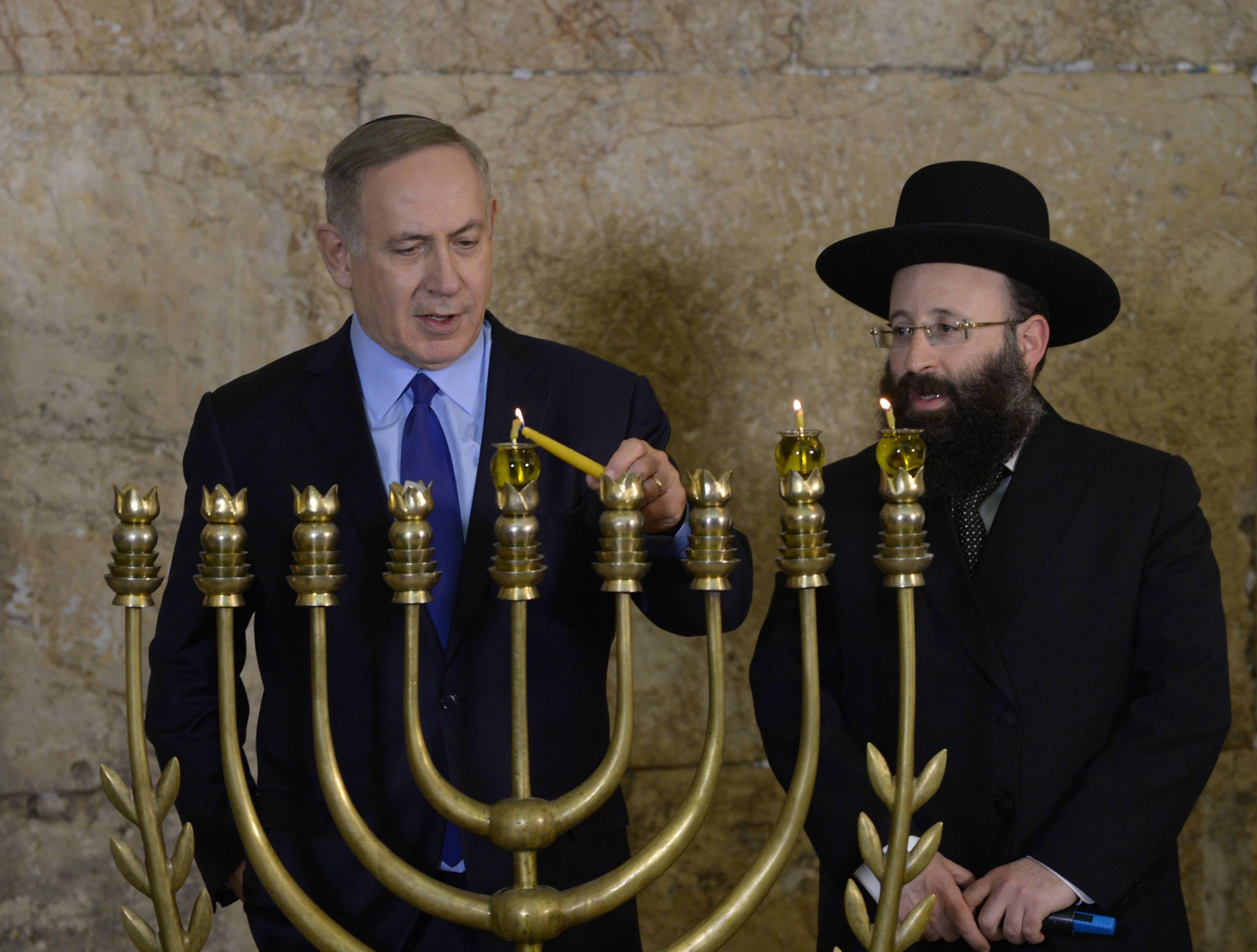 Israeli Prime Minister Benjamin Netanyahu lights the menorah for the second night of Hanukkah at the Western Wall in Jerusalem on December 25, 2016
