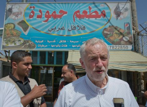 United Kingdom's Labour party leader Jeremy Corbyn walks in the main market road during his visit to the Zaatari Syrian Refugee Camp, in Mafraq, Jordan, Friday, June 22, 2018.