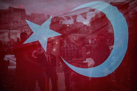 In this photo taken late Sunday, June 24, 2018, seen behind a Turkish flag, supporters of Turkey's President and ruling Justice and Development Party, or AKP, leader Recep Tayyip Erdogan, gather during celebrations outside the party headquarters in Istanb