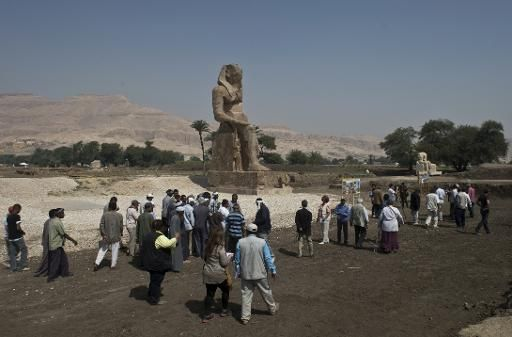 Tourists and journalists walk past a newly displayed statue of pharaoh Amenhotep III in Egypt's temple city of Luxor on March 23, 2014