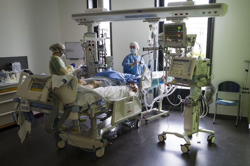 Le personnel médical travaille devant un patient dans une unité de soins intensifs de niveau pour les patients contaminés par un coronavirus COVID-19 de l'hôpital Louis Pasteur de Colmar, dans l'est de la France, le 26 mars 2020