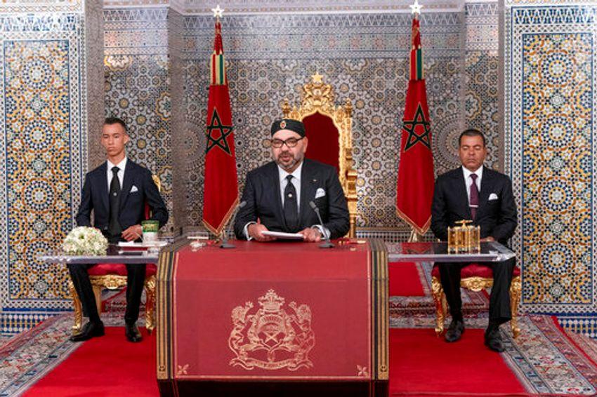 العاهل المغربي محمد السادس ، وسط ، برفقة نجله ولي العهد الأمير مولاي حسن ، إلى اليسار ، وشقيقه الأمير مولاي راشد يخاطب الأمة في كلمة بثها التلفزيون ، في القصر الملكي. في تطوان ، المغرب