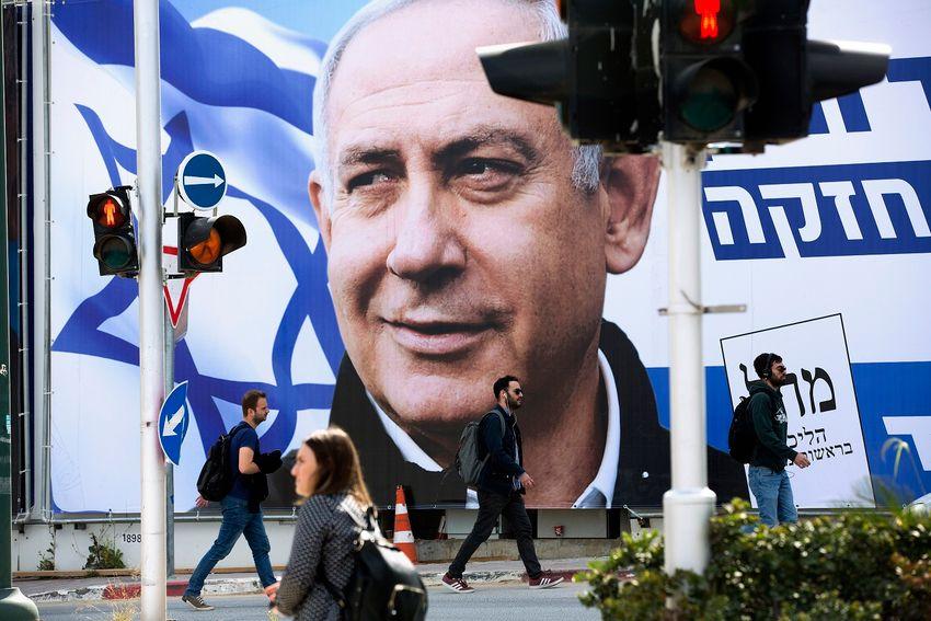 As pessoas caminham por um cartaz da campanha eleitoral mostrando o primeiro-ministro de Israel Benjamin Netanyahu, líder do partido Likud, em Tel Aviv, Israel, quinta-feira, 28 de março de 2019.