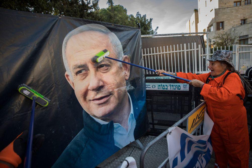 Manifestantes anti-Netanyahu vestidos como faxineiros manifestam-se do lado de fora da residência oficial do primeiro-ministro israelense na rua Balfour, em Jerusalém, 8 de fevereiro de 2021.
