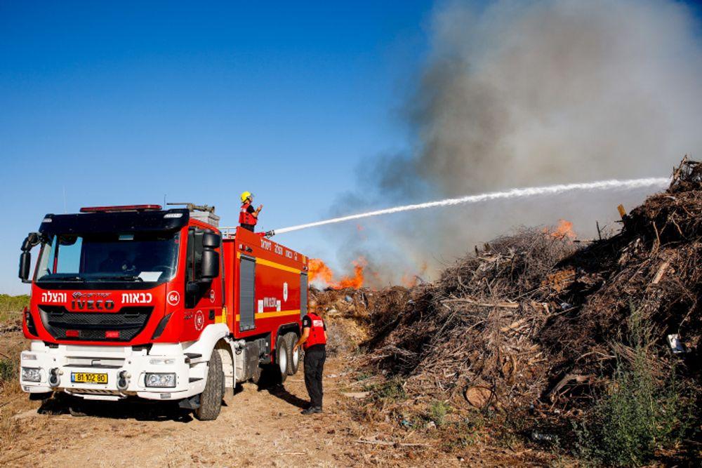 Bombeiros tentando apagar um incêndio na floresta Simhoni causado por balões incendiários lançados por terroristas palestinos no sul de Israel em 15 de junho de 2021.