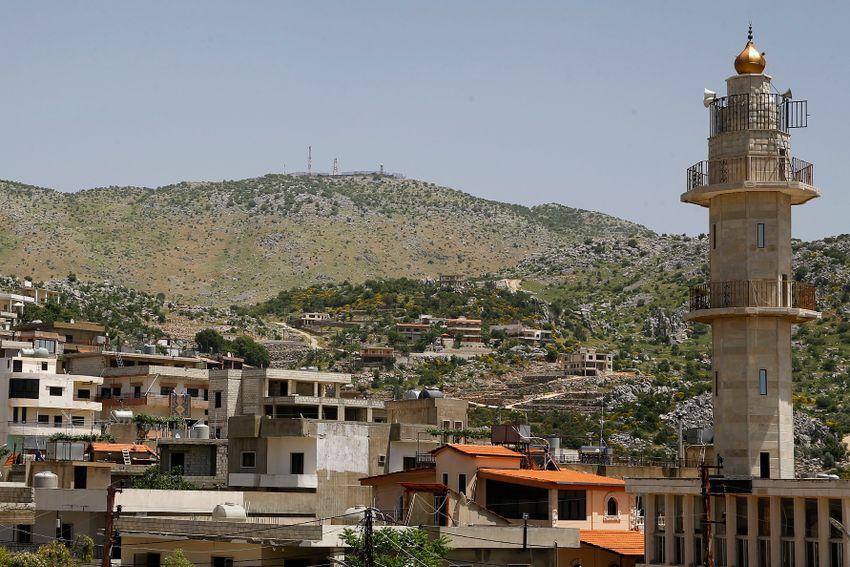 DOSSIER - Un poste militaire israélien au sommet du mont Hermon dans les hauteurs du Golan contrôlées par Israël est vu du village de Kfar Chouba, où les frontières israélo-syro-libanaises se rejoignent, dans le sud-est du Liban, le 20 mai 2020.
