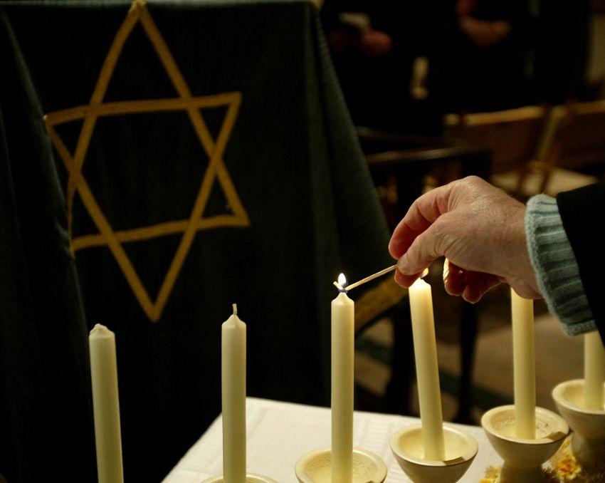 Uma mulher acende uma vela durante uma cerimônia em 26 de janeiro de 2006, na véspera do dia em memória do Holocausto.