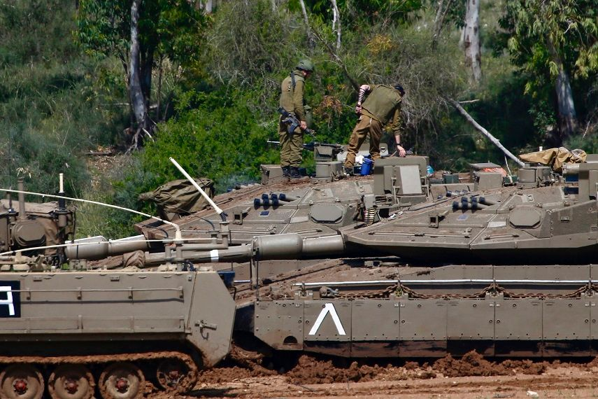 Israeli soldiers work next to their tanks near the Israel Gaza border, Israel, Tuesday, March 26, 2019.