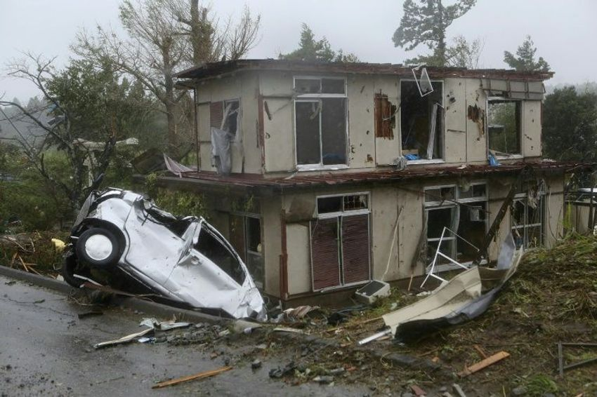 A vehicle lies in a ditch next to a badly damaged house in Chiba prefecture, east of Tokyo, after strong winds brought by Typhoon Hagibis hit the area
