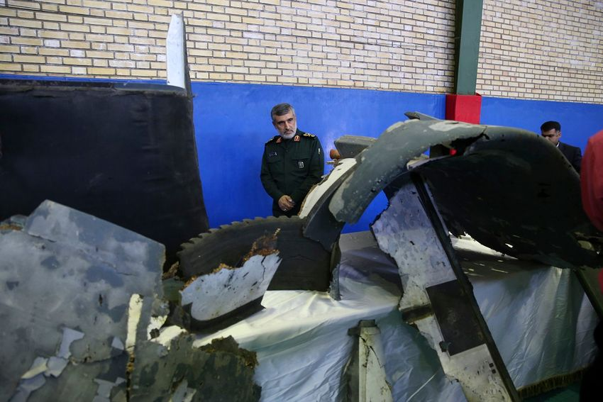 Head of the Revolutionary Guard's aerospace division Gen. Amir Ali Hajizadeh looks at debris from what the division describes as the U.S. drone which was shot down on Thursday, in Tehran, Iran, Friday, June 21, 2019.