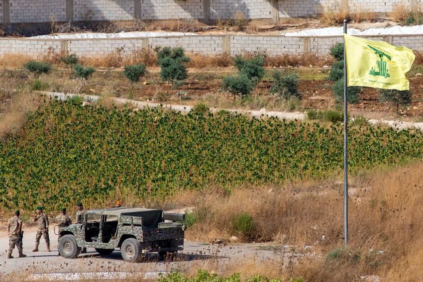 Lebanese soldiers next to a Hezbollah flag patrol in the southern Lebanese village of Aitaroun, on the Israel-Lebanon border, Israel, Tuesday, Aug. 27, 2019.