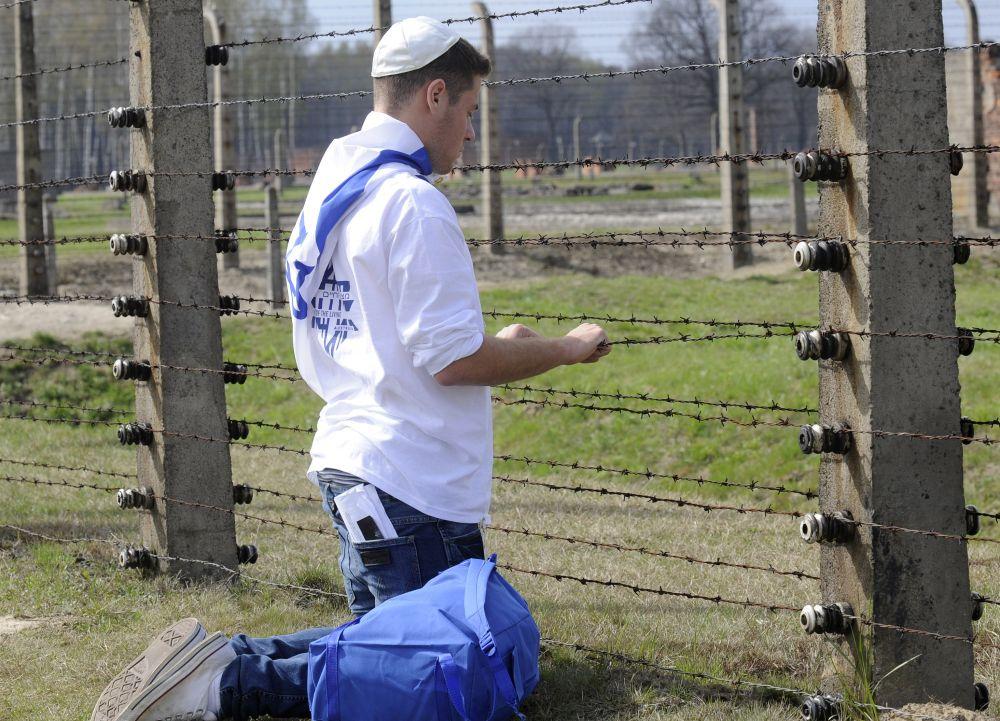 Un jeune juif prie près d'une clôture en fil de fer barbelé lors de la marche annuelle des vivants dans l'ancien camp de la mort nazi d'Auschwitz-Birkenau, à Oswiecim, dans le sud de la Pologne, le 19 avril 2012.