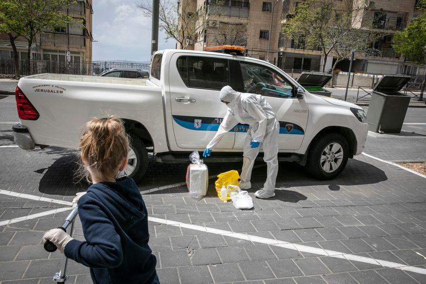 Des membres de l'équipe médicale de Magen David Adom, portant un équipement de protection, effectuent des tests de coronavirus auprès de patients à Jérusalem, le 17 avril 2020
