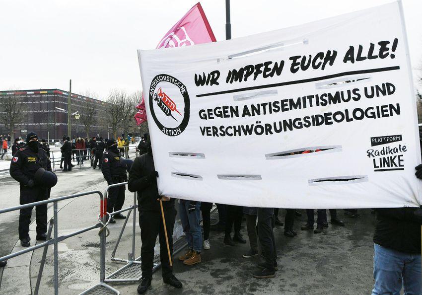 """Une banderole indique """"Nous vous vaccinons tous contre l'antisémitisme et les théories du complot"""" lors d'une manifestation sur le thème """"Pas de scène pour les idéologues du complot"""", sur la Heldenplatz à Vienne le 16 janvier 2021"""